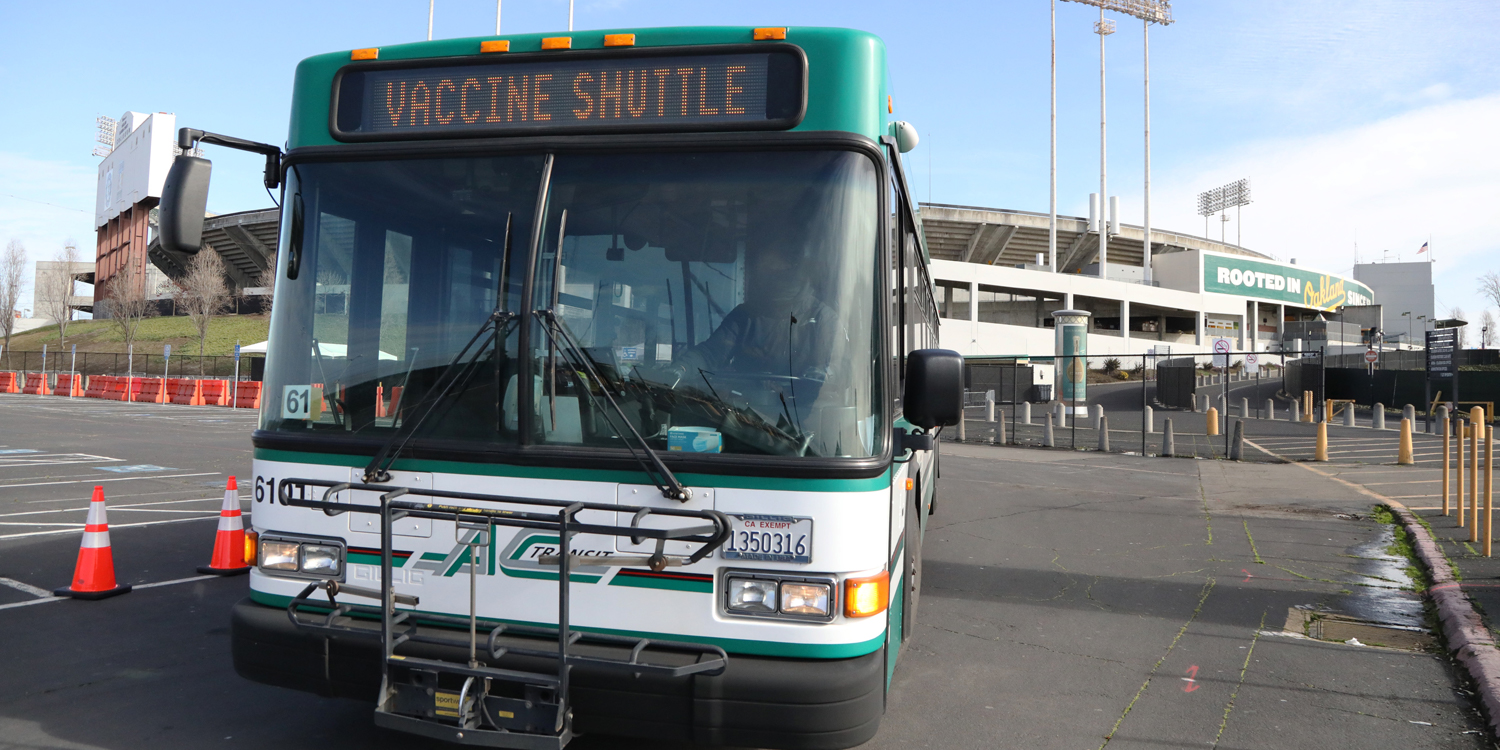 AC Transit Vaccine Shuttle bus with Oakland Coliseum in background