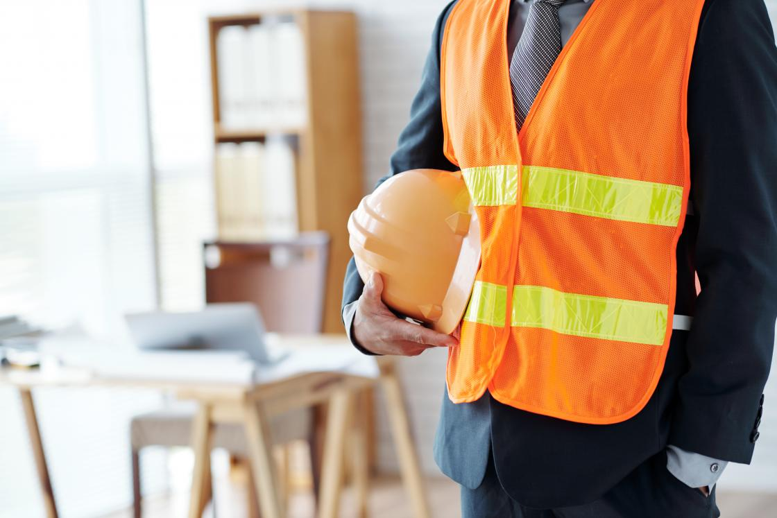 torso of man wearing safety vest and carrying a hard hat